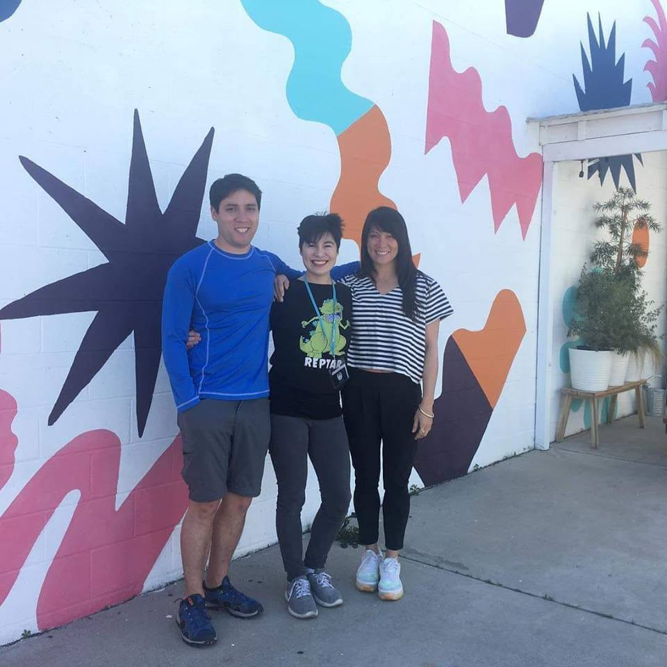 Three people stand together in front of a colorful mural at Writers Blok.
